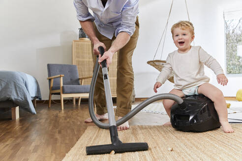 Low section of man cleaning carpet while cute baby boy sitting on vacuum cleaner in living room at home - FSF01075
