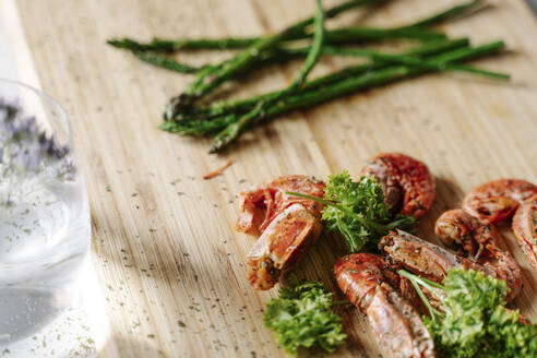 Grilled prawns, parsley and asparagus on wooden cutting board - JMHMF00047