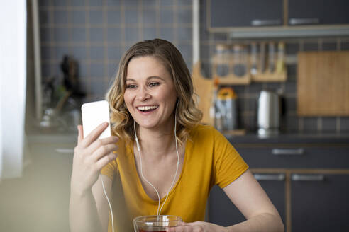 Happy woman having a video chat with smartphone in kitchen at home - VPIF02456