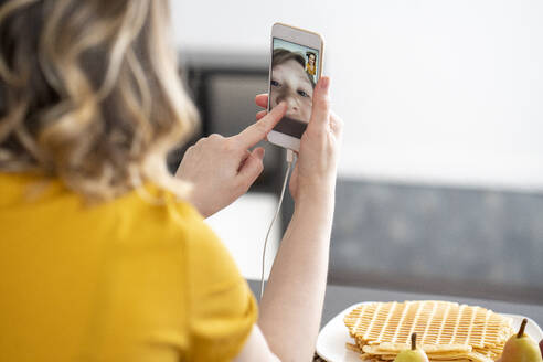 Woman having a video chat with her son on smartphone - VPIF02462