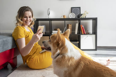 Woman with dog using smartphone in living room at home - VPIF02468