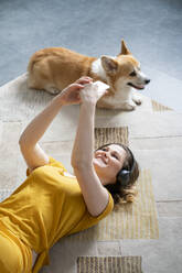 Woman with dog and headphones lying on the floor at home using smartphone - VPIF02477