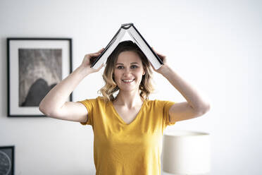 Portrait of smiling woman at home holding book above her head - VPIF02483