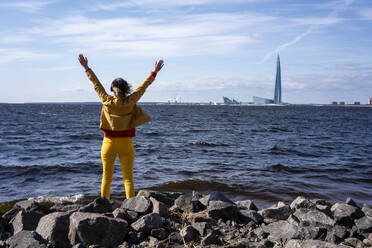 Rear view of woman standing at the coast with raised arms, Saint Peterburg, Russia - VPIF02489