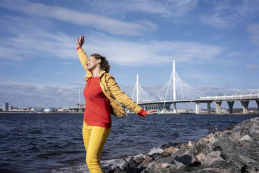 Carefree woman standing at the coast, Saint Peterburg, Russia - VPIF02492