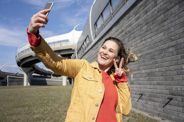 Happy woman with windswept hair taking a selfie at a brick wall - VPIF02498