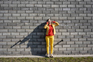 Smiling woman standing at a brick wall listening to music with headphones - VPIF02501