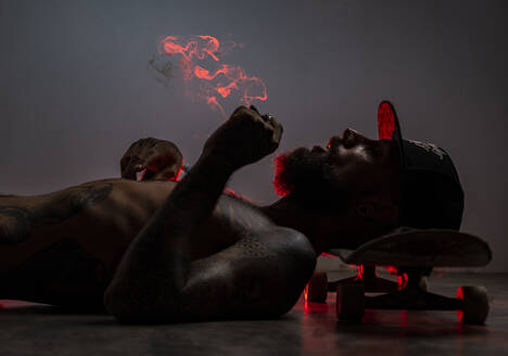 Tattooed skateboarder lying on the floor smoking a joint - AMUF00110