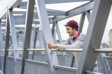 Stylish young man using smartphone on a bridge - DIGF10905