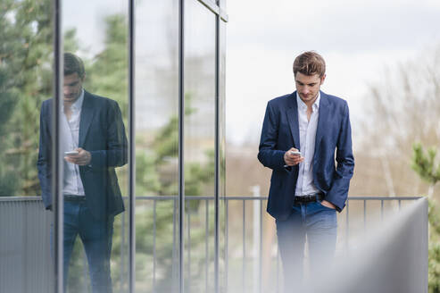 Young businessman using smartphone at an office building - DIGF10926