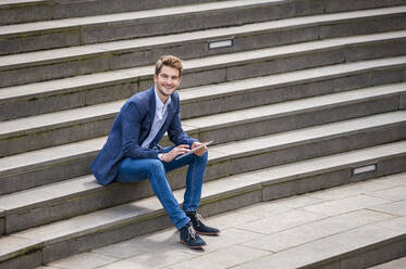 Happy young businessman sitting on stairs using tablet - DIGF10929
