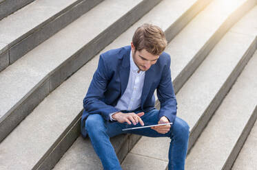 Young businessman sitting on stairs using tablet - DIGF10932