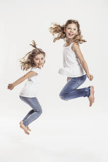 Portrait of two barefoot sisters jumping in the air in front of white background - SDAHF00938