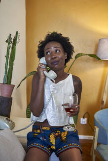Woman holding a glass of wine and using old-fashioned landline phone in living room at home - VEGF02242
