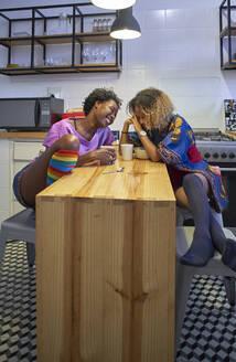 Two happy women sitting in the kitchen - VEGF02245