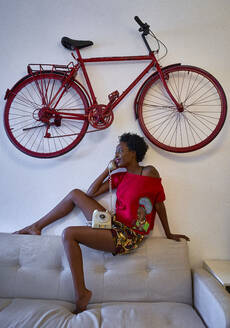 Woman using old-fashioned landline phone in living room at home with bicycle hanging on the wall - VEGF02251