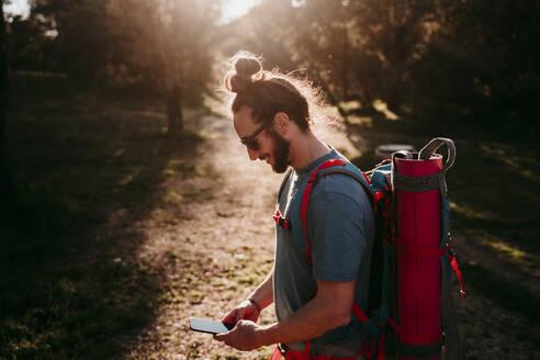 Bearded man with smartphone on a hiking trip - EBBF00022