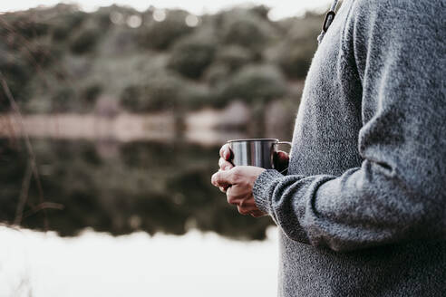 Close-up of man holding mug at lakeside - EBBF00070