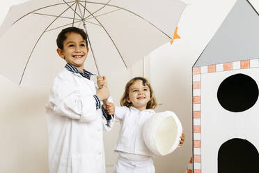 Siblings playing astronaut and researcher with umbrella at rocket - JRFF04462