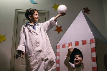 Siblings playing astronaut and researcher at home - JRFF04468