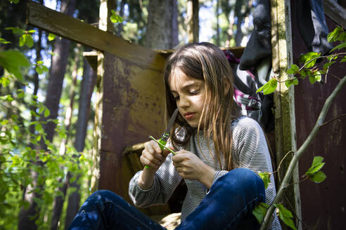 Girl carving a piece of wood sitting on raised hide in the woods - LVF08887