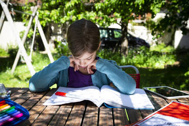 Girl sitting at garden table doing homework - LVF08890