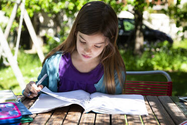 Girl sitting at garden table doing homework - LVF08893