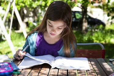 Girl sitting at garden table doing homework - LVF08893