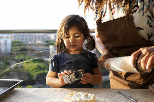 Portrait of little girl baking cookies with her mother - VABF02920