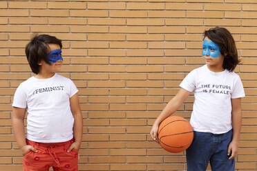 Portrait of two brothers with painted blue masks on their faces wearing t-shirts with feministic imprints - VABF02926