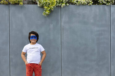 Portrait of boy with painted blue mask on his face wearing t-shirt with imprint 'Feminist' - VABF02932