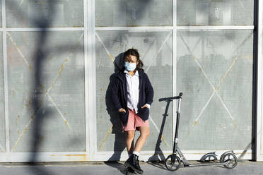 Portrait of boy wearing protective mask with scooter in the city - VABF02962