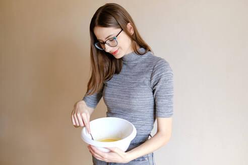 Woman in t-shirt and jeans preparing homemade cupcakes in her kitchen - CAVF80963