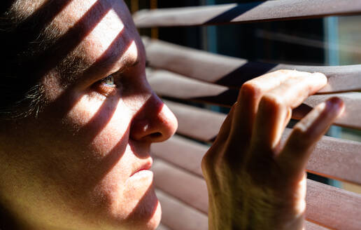 Adult woman with blue eyes opening a wooden curtain with her fingers to look through the window while the sunlight creates sun and shadow on her face. Horizontal photo. - CAVF80966