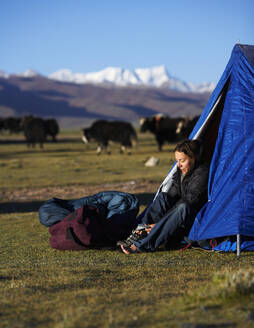 Woman putting her boots on at camp in Tibet - CAVF81035