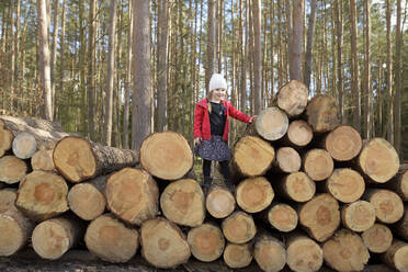 Little girl standing on stack of wood in the forest - BRF01462