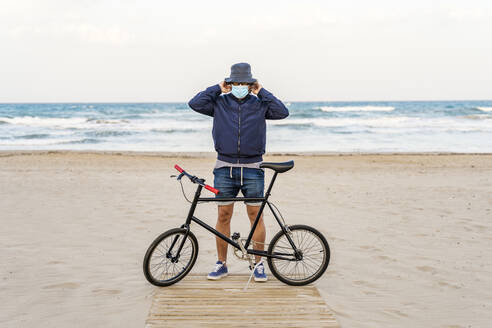 Mature man with bicycle, standing on the beach, wearing face mask - DLTSF00684