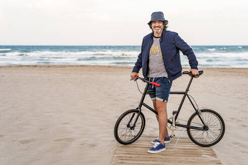 Mature man with bicycle, standing on the beach, smiling - DLTSF00687