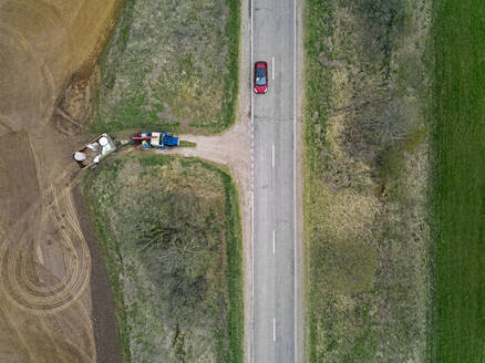 Russia, Aerial view of car driving along country road passing tractor plowing adjacent field - KNTF04644