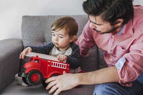 Baby boy sitting on couch with his father playing with fire engine toy car - FLMF00226