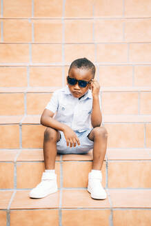 Portrait of cool little boy wearing sunglasses sitting on stairs outdoors - OCMF01221