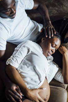 Affectionate man with pregnant young woman on couch - OCMF01233