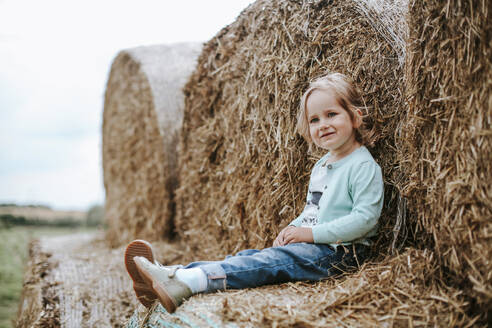 Portrait of smiling girl sitting on straw bales - VBF00068