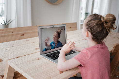 Girl sat talking and waving to a nurse on a video call at home - CAVF81874