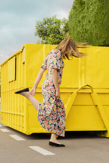 Woman in flower dress, jumping in the street in front of yellow container - ERRF03830