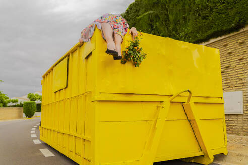Woman lying on top of yellow container, holding buch of flowers - ERRF03854