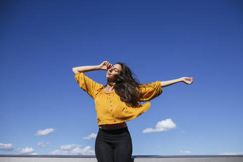 Carefree woman dancing on roof terrace in sunlight - GMLF00219