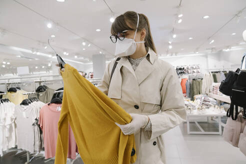 Woman with face mask and disposable gloves shopping in a fashion store - AHSF02591