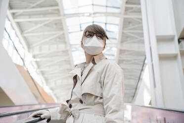 Woman with face mask and disposable gloves on an escalator in a shopping center - AHSF02594