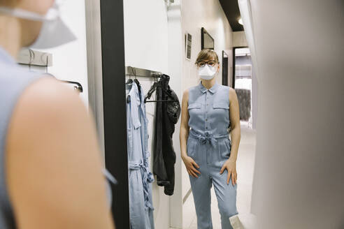 Woman with face mask trying on clothes in a fashion store - AHSF02597
